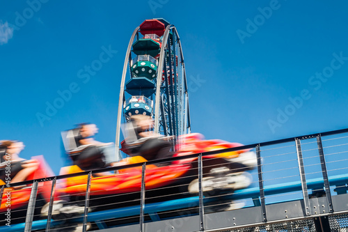 Ferris wheel and roller coaster in motion in amusement park