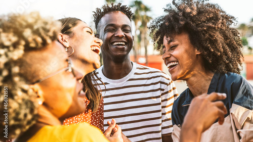 Young happy people laughing together - Multiracial friends group having fun on city street - Diverse culture students portrait celebrating outside - Friendship, community, youth, university concept.