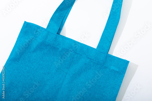 Composition of empty blue canvas shopping bag lying flat on white background