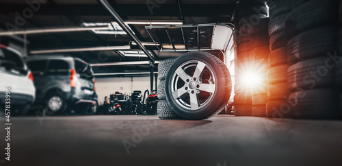 tire at repairing service garage background. Technician man replacing winter and summer tyre for safety road trip. Transportation and automotive maintenance concept