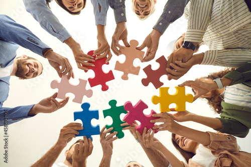 Group of young and mature people making circle of colorful jigsaw puzzle parts, low angle shot from below. Happy business team enjoying teamwork, finding professional solution, starting new enterprise