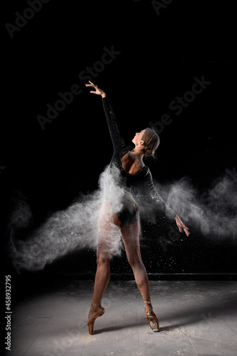 Art perfomance. Full-length portrait of talented flexible ballet dancer moving in cloud of dust, young dancer in flour. Isolated over black studio background. Dance, people, art, performance concept