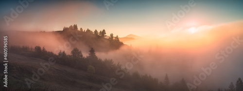 Panorama of valley covered with fog in a light