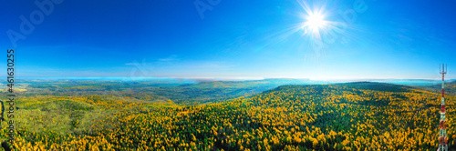 Panorama from height to autumn forest and trees. Flying over the forest on bright sunny autumn day. Flight over the mountains