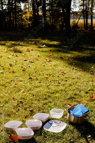kempingowe naczynia suszące sie na trawie w słońcu, kemping w letni słoneczny dzień